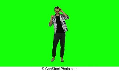 Man looking into a virtual reality glasses. Green screen