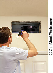 Man Looking into Air Duct - Adult male shining a flashlight ...