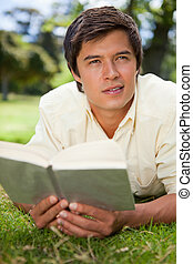 Man looking into the distance while reading a book as he lies prone in the grass