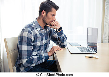 Man looking on laptop at home