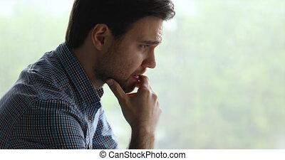 Close up view man looking into distance out window feels unhappy goes through divorce break up having mental pain. Marriage split, drug addiction alcohol abuse, need help rehab treatment aid concept