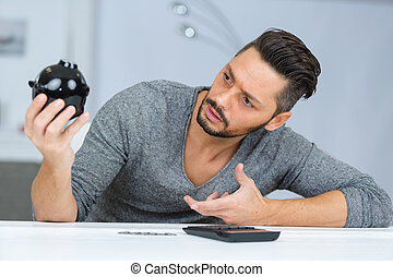 man looking questioningly at piggy bank