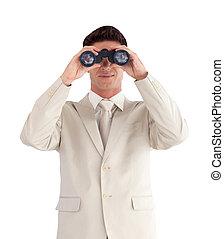 Man looking straight ahead through a binnoculars -...