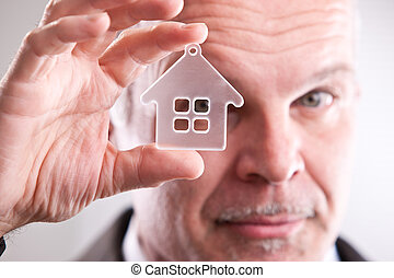 Man looking through a little house in front of you