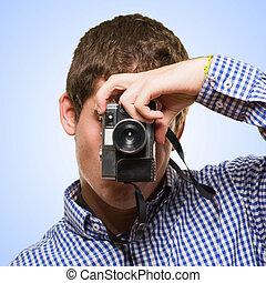 Man Looking Through A Vintage Camera