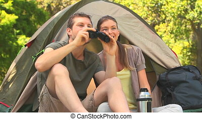 Man looking through binoculars - Couple sitting outside tent...