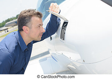 Man looking through open flap on aircraft