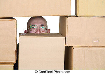 Man looking through pile of cardboard boxes - Man looking...
