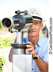 Man looking through telescope