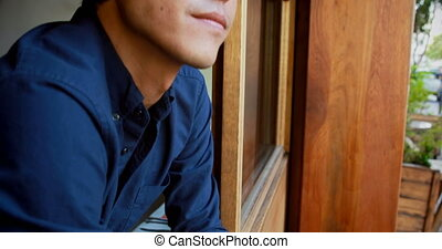 Man looking through window at outdoor cafe 4k - Young man...