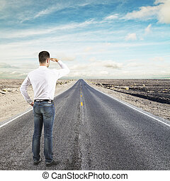 man standing on road looking to horizon