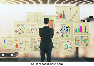 Man looking to the business graphs on the glass window in a modern office