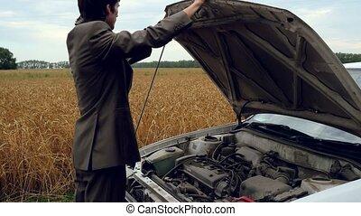 Man looking under hood of old car in countryside. 4k