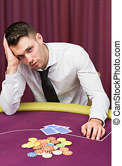 Man looking unhappy at poker table