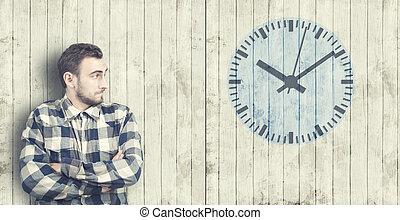 Man looks at a clock