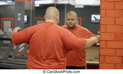 Man looks at himself in mirror of sport gym