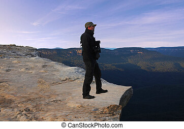 Man looks at the landscape from Lincoln Rock Lookout at sunrise of the Grose Valley located within the Blue Mountains New South Wales Australia