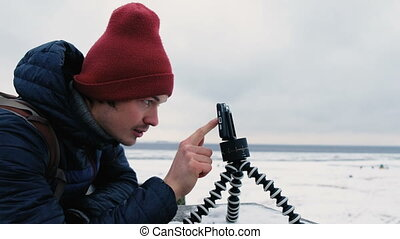 Man looks at the phone on a tripod and touches the screen in winter, 4K.