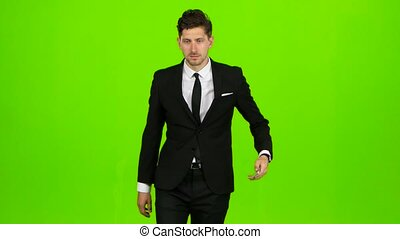 Man looks at the photos on the phone and on the move scrolls through the list of pictures, he has a good mood, he smiles. Green screen