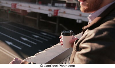 Man looks at traffic in the city, drinking coffee