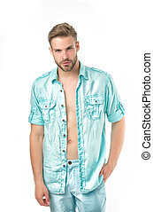 Man looks attractive in unbuttoned casual linen blue shirt. Man on calm face posing confidently with hand in pocket, white background. Guy with bristle wears casual or formal shirt. Fashion concept