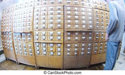 Man looks for books in library cardfile, time lapse