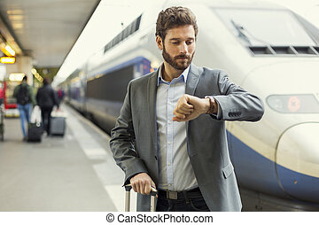 Man looks his watch on the platform station