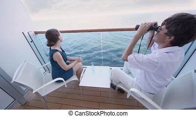 man looks in field-glass at sea and transfers it to woman...