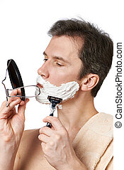 Man looks in mirror and shaving
