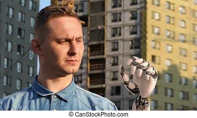 Man Looks on His Robotic Hand