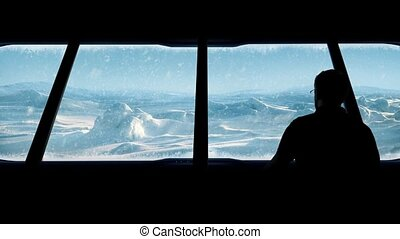 Man Looks Out From Arctic Base - Man goes to window in...