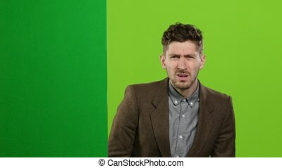 Man looks out from behind a green board and shouts a lot. Green screen