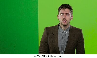 Man looks out from behind a green board and shouts a lot. Green screen. Slow motion