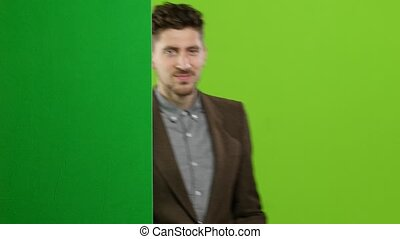 Man looks out from behind the green board and waves. Green screen