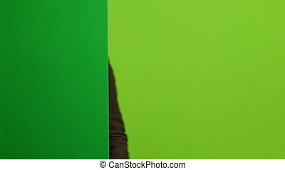 Man looks out from behind the green board, makes grimaces, and hides. Green screen