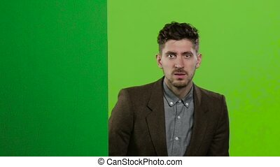 Man looks out from behind the green board, makes grimaces, and hides. Green screen. Slow motion