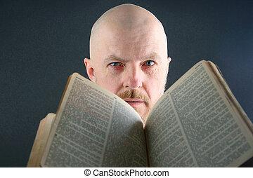 man looks through an open Bible