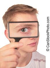 man looks through magnifier