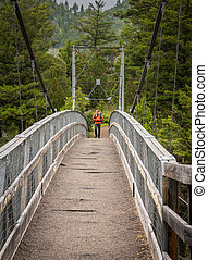 Man Looks to Side While Standing Across Bridge in Yellowstone