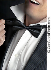 A close-up shot of a man wearing a tux loosening his bowtie.