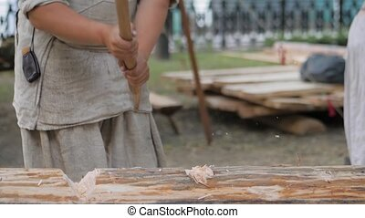 Man lumberjack cutting large log with axe - wood shavings, chips flying at summer historical medival festival - close up, slow motion. Craftsmanship, revival, reenactment, handwork concept