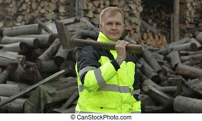 Lumberjack posing in green jacket with reflective stripes and holds big axe. Thumb up. Man woodcutter standing and looking at camera. Sawn logs, firewood background. Sawmill, wood harvesting