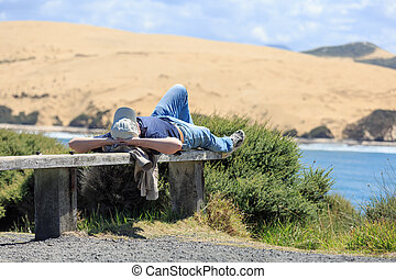 Man lying and relaxing on a bench