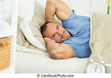 man lying asleep in cozy white pillow under blanket