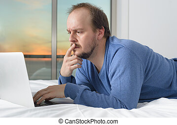 man lying bed working laptop