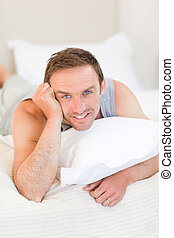 Man lying down on his bed