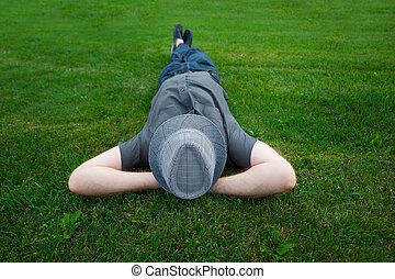 man lying in a field on green grass with the hat over his face
