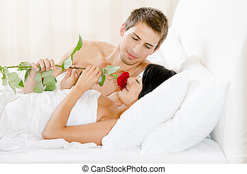Man lying in bed gives red rose to girl