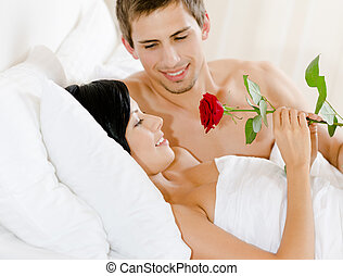 Man lying in bed gives scarlet rose to woman