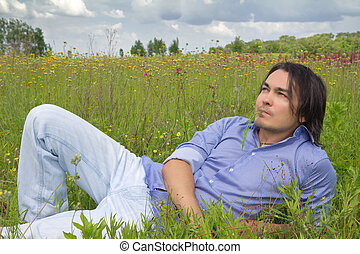 Man lying on a spring blossom meadow